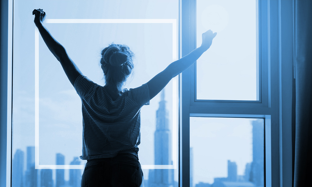 Woman stretching after waking up and checking out the view from her window.